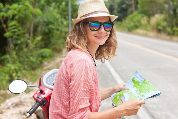 Bella giovane donna con mappa in mano e una moto sulla strada. viaggi, navigazione, turismo