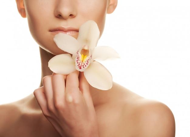 Bella giovane donna con orchidea bianca