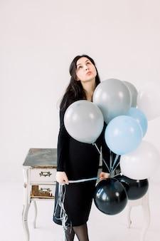 Bella giovane donna con palloncini su uno sfondo bianco, in piedi vicino al tavolo bianco vintage e guardando in alto. compleanno e festa. ragazza in abito nero al festival