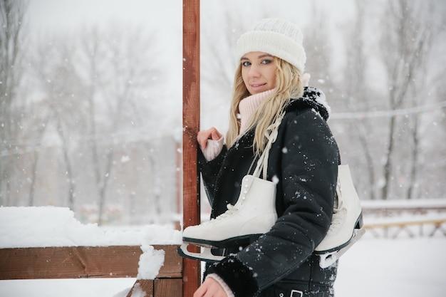 Bella giovane donna con pattini da ghiaccio, copia spazio