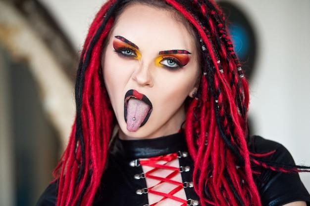Bella giovane donna con piercing, teme e trucco alla moda. cyberpunk donna.