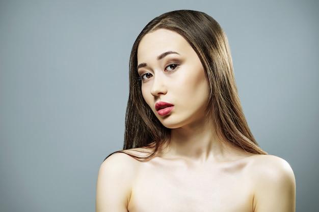Bella giovane donna con trucco naturale e pelle pulita