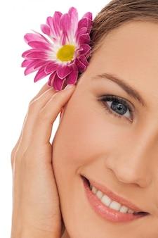 Bella giovane donna con un fiore tra i capelli