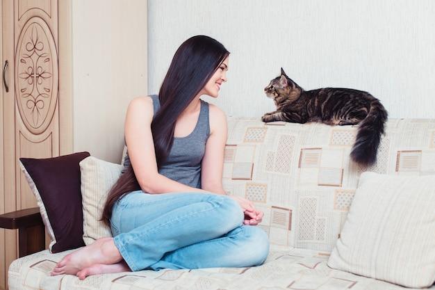 Bella giovane donna con un gatto di casa sul divano