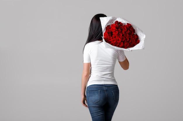 Bella giovane donna con un grande mazzo di rose rosse