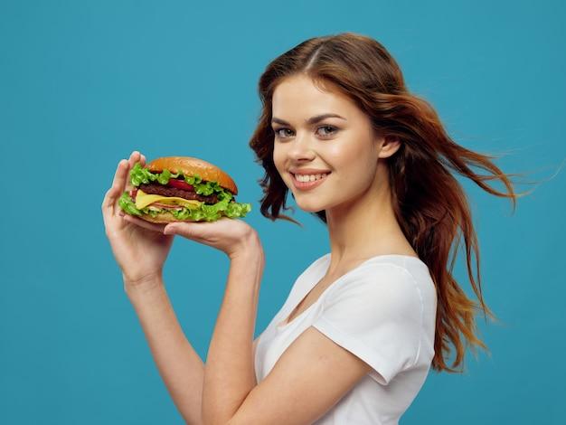 Bella giovane donna con un succoso hamburger nelle sue mani, una donna che mangia un hamburger