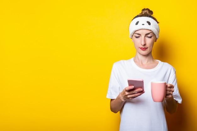 Bella giovane donna con un telefono e una tazza di caffè su uno sfondo giallo