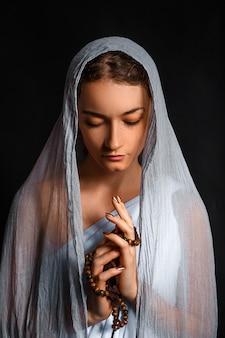 Bella giovane donna con una sciarpa in testa e un rosario tra le mani, sguardo umile, donna credente.