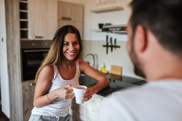Bella giovane donna con una tazza di caffè con il suo fidanzato.