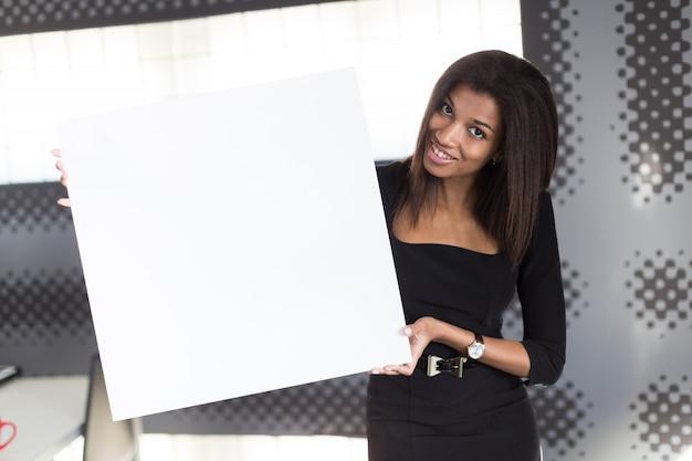Bella giovane donna d'affari in nero forte suite tenere vuoto cartello bianco