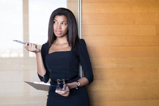 Bella, giovane donna d'affari in nero forte tablet suite stretta