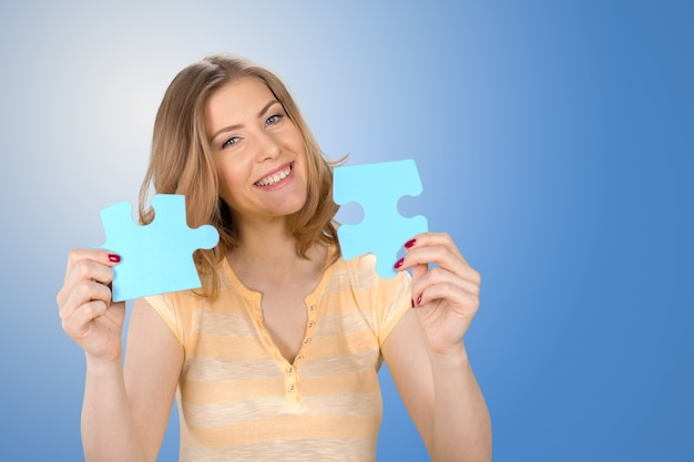 Bella giovane donna d'affari in possesso di un pezzo di puzzle blu