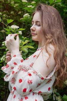 Bella giovane donna dagli occhi azzurri in un vestito leggero si trova in un parco in una giornata di sole.