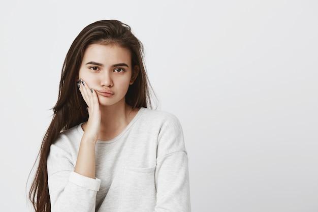 Bella giovane donna dagli occhi scuri con i capelli lunghi scuri che indossa maglione sciolto, tenendo la mano sulla guancia, guardando con espressione seria