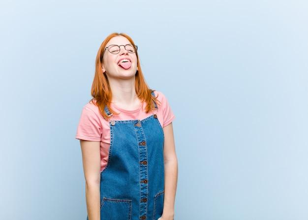 Bella giovane donna dai capelli rossi con atteggiamento allegro, spensierato, ribelle, scherzando e tirando fuori la lingua, divertendosi