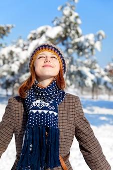 Bella giovane donna dai capelli rossi in winter park