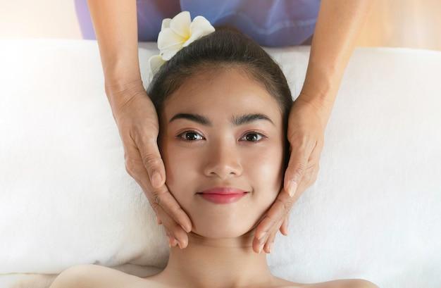 Bella giovane donna dell'asia che ottiene trattamento della stazione termale con il fronte pulito della pelle fresca