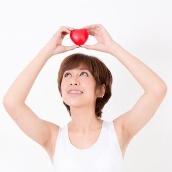 Bella giovane donna dell'asia con cuore rosso sulla sua testa. isolato su sfondo bianco illuminazione da studio. concetto per la salute.
