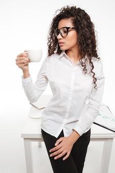 Bella giovane donna di affari africana in vetri che stanno e che bevono caffè