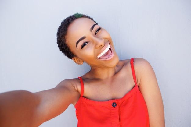 Bella giovane donna di colore che prende selfie