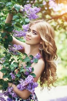 Bella giovane donna di modo all'aperto circondata da estate dei fiori lilla.