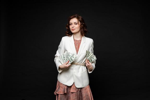 Bella giovane donna dopo lo shopping sta con un sacco di pacchetti e soldi nelle sue mani
