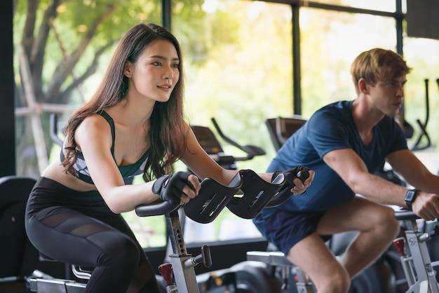 Bella giovane donna ed uomo che si esercitano sulla bici fissa al club di sport della palestra di forma fisica
