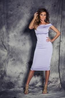 Bella giovane donna elegante con capelli castano chiaro, trucco e acconciatura moda, posa in abito da cocktail lilla aderente e tacchi dorati