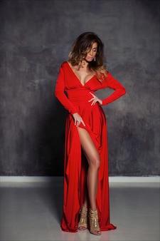 Bella giovane donna elegante con capelli castano chiaro, trucco e acconciatura moda, posa in abito da sera lungo rosso aderente e tacchi dorati
