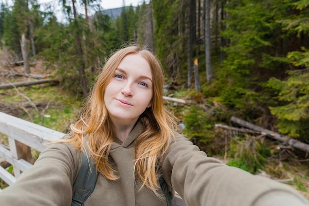 Bella giovane donna escursionista prendendo selfie nella foresta di montagna