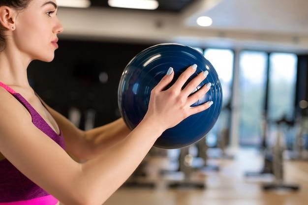 Bella giovane donna esile in sportwear che fa una certa ginnastica alla palestra con il medball