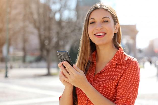 Bella giovane donna felice che guarda l'obbiettivo e che tiene il telefono cellulare all'aperto con strada sfocata sullo sfondo.