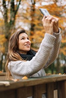Bella giovane donna felice che prende selfie con lo smartphone nel parco di autunno. concetto di stagione, tecnologia e persone.