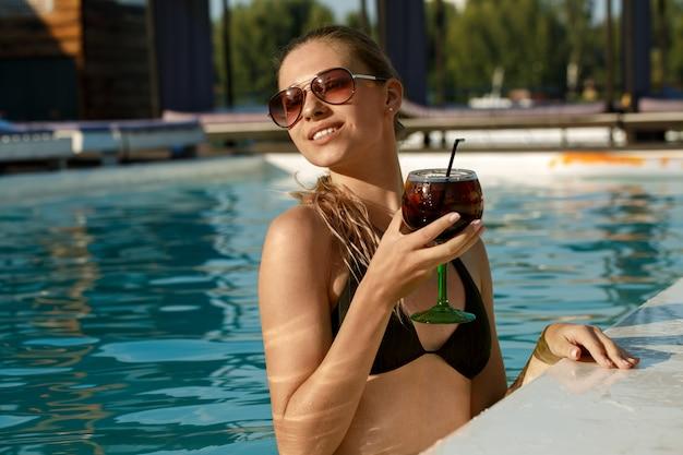 Bella giovane donna felice che si rilassa nella piscina