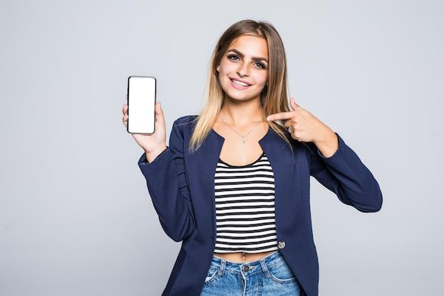 Bella giovane donna felice che tiene telefono cellulare dello schermo in bianco e dito puntato sopra il muro bianco