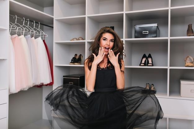 Bella giovane donna felice con capelli ricci marroni lunghi piacevolmente sorpreso, scioccato tanti bei vestiti nel guardaroba di lusso. il modello alla moda ha un aspetto elegante, indossa un abito elegante nero.