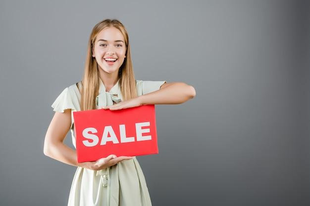 Bella giovane donna felice emozionante con il segno di vendita isolato sopra grey