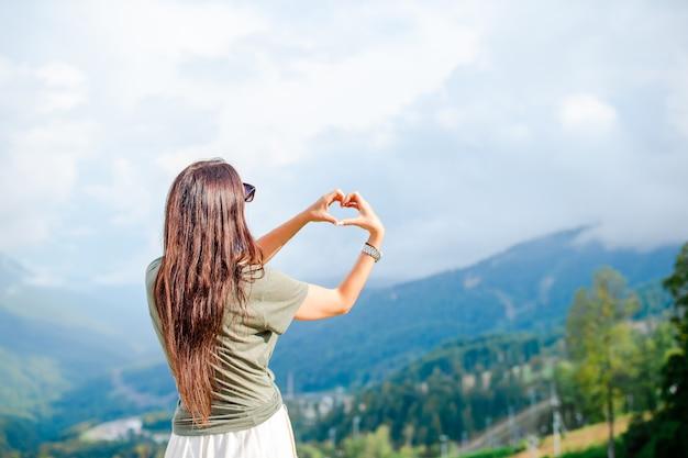 Bella giovane donna felice in montagna