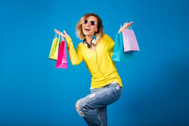 Bella giovane donna hipster, che tiene le borse della spesa di carta colorata