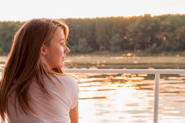 Bella giovane donna in abiti bianchi seduti sulla riva del fiume in