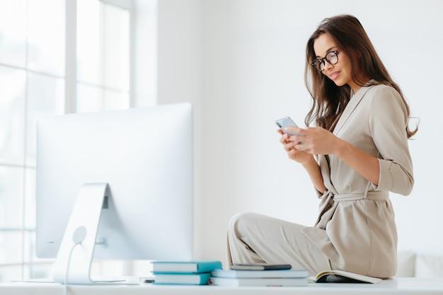Bella giovane donna in abiti eleganti controlla newsfeed tramite smartphone