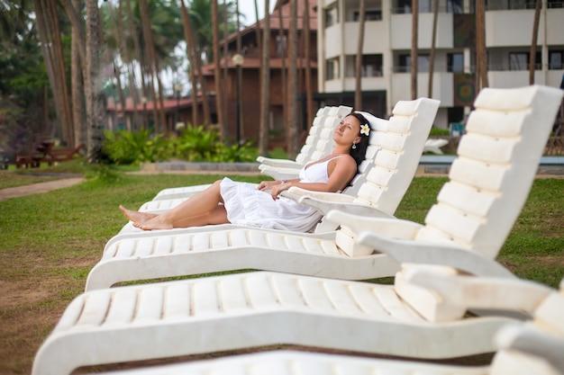 Bella giovane donna in abito bianco sdraiato su un lettino in riva al mare.