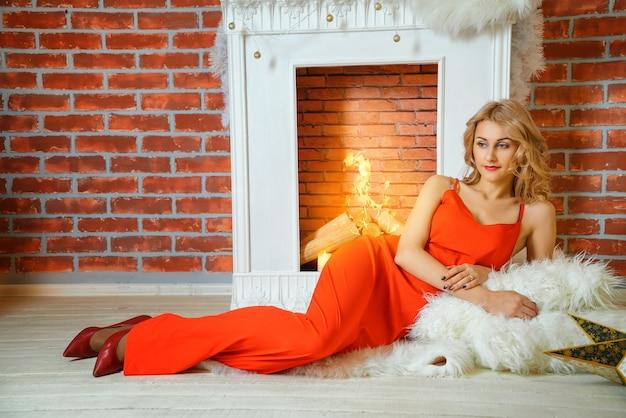 Bella giovane donna in abito rosso sdraiato accanto al caminetto