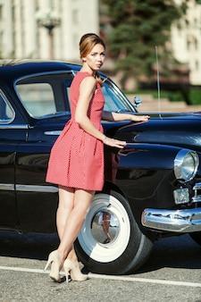 Bella giovane donna in abito vintage con auto retrò