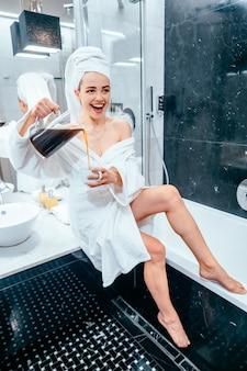 Bella giovane donna in accappatoio e asciugamano sulla sua testa che si siede su una vasca