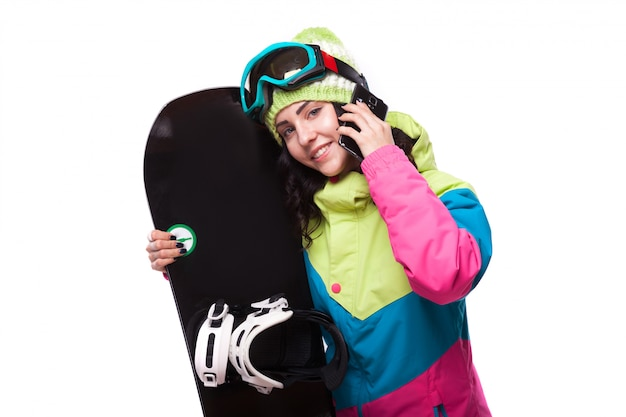 Bella giovane donna in attrezzatura da sci e tenere snowboard