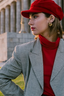 Bella giovane donna in berretto rosso con orecchino d'oro nelle sue orecchie guardando lontano
