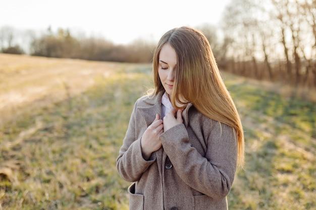 Bella giovane donna in cappotto di lana sulla foresta al tramonto