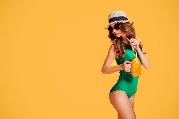 Bella giovane donna in costume da bagno color smeraldo e brocca con cappello di paglia con bevanda fredda