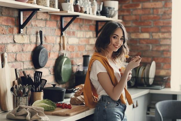 Bella giovane donna in cucina